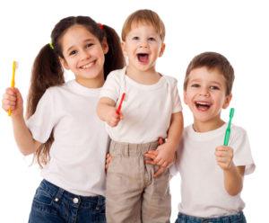 Edmonton Pediatric Dentistry - Children smiling while holding toothbrushes.