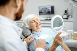 elderly woman smiling after getting dental implants